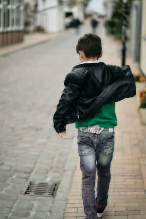 teenager boy in hoodie and leather jacket walks away on city street. 版權商用圖片