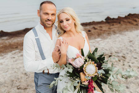 happy just married couple on the beach with wedding bouquet in bohe style. Wedding on the beach
