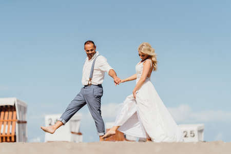 happy pretty newly married couple walking on the beach. Wedding on the beach