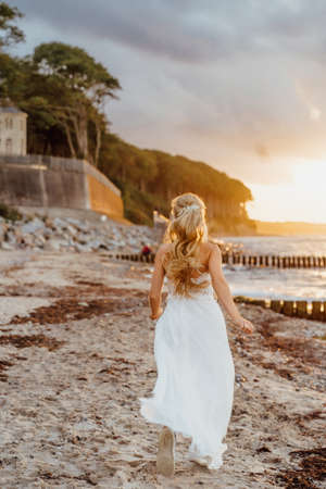 bride on the beach. Young woman in white dress runs on the beach in sunlight