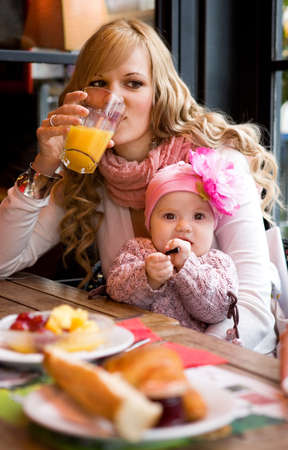 motherhood: Young mother and baby daughter having breakfast together in a Parisian cafe