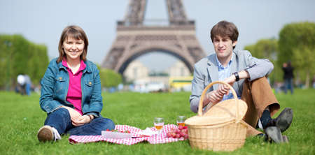 Happy young couple having a picnic near the Eiffel Tower photo