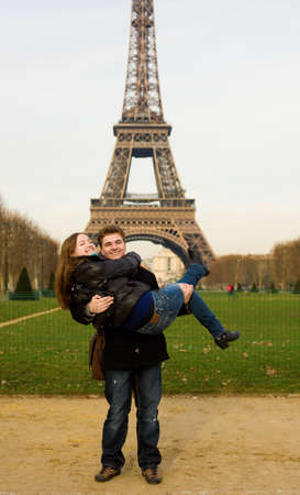Happy romantic couple having fun near the Eiffel Tower in Paris. Boyfriend is carrying girlfriend in his arms