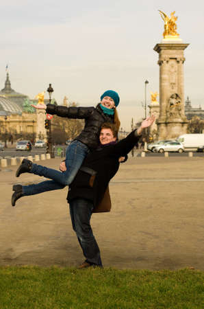 Happy couple in Paris having fun near the Pont Alexandre III, boyfriend carrying girlfriend in his arms photo