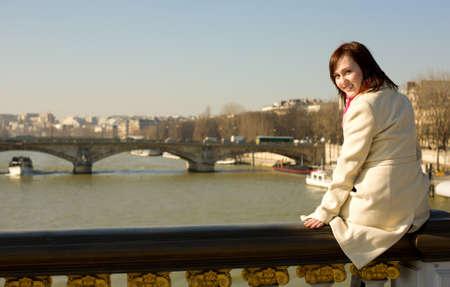 balustrade: Happy beautiful girl in Paris sitting on the balustrade of Pont Alexandre III
