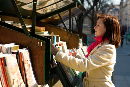 antiquary: Beautiful woman in Paris selecting a book in an outdoor bookseller box