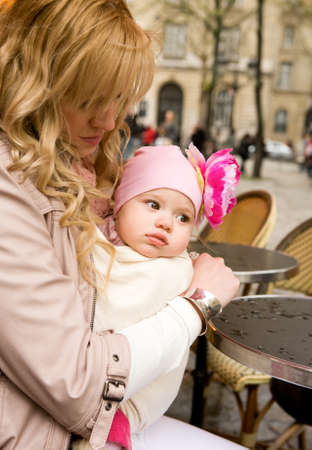 Beautiful young mother with her baby daughter in a Parisian street cafe photo