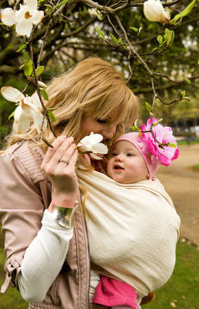 Beautiful young mother with her baby daughter in a garden at spring Stock Photo