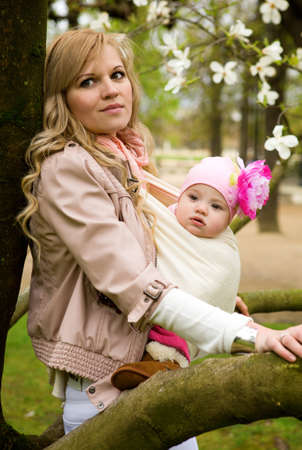 Beautiful young mother with her baby daughter in a garden at spring photo
