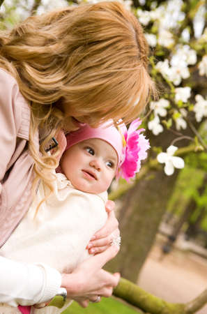 Beautiful young mother with her baby daughter outdoors at springtime photo