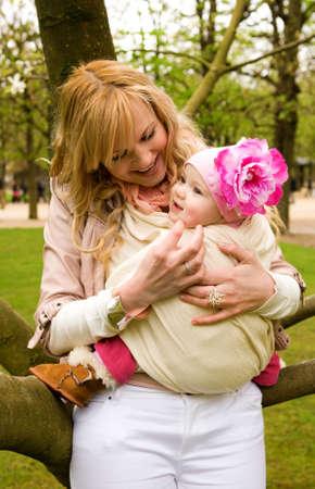 draagdoek: Mooie jonge moeder en baby dochter plezier buitenshuis op lente Stockfoto