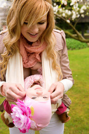 Young mother and baby daughter having fum outdoors photo