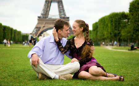 Happy romantic couple in Paris, sitting on grass by the Eiffel Tower photo
