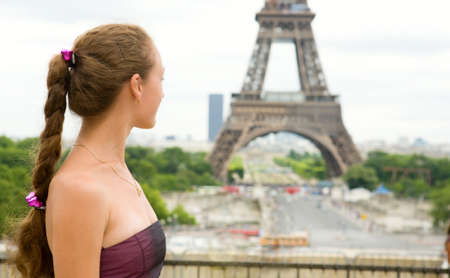Young beautiful girl in Paris, looking at the Eiffel Tower photo