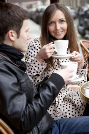Young couple in a Parisian street cafe, drinking coffee photo