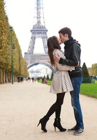 Young romantic couple kissing near the Eiffel Tower in Paris photo