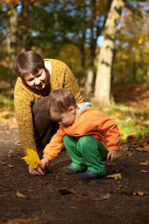 Mother and son playing with leaves at fall photo
