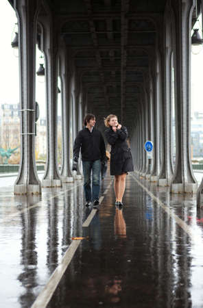 Bad weather in Paris. Couple on the Bir-Hakeim bridge at rain photo