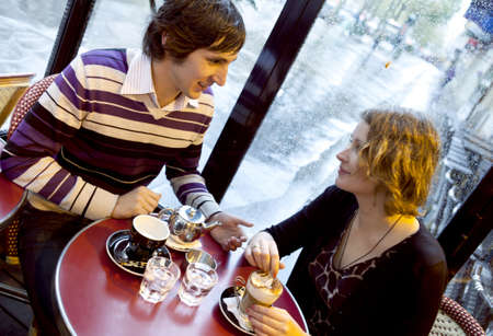 parisian: Happy couple in a Parisian cafe at rain Stock Photo