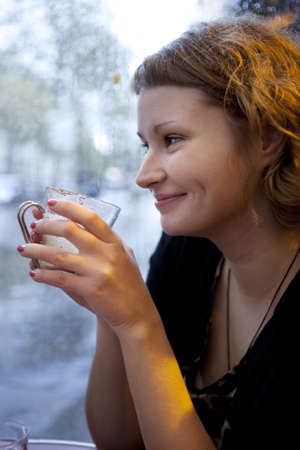 Beautiful smiling girl drinking cappuccino in a Parisian cafe at rain Stock Photo - 9896984