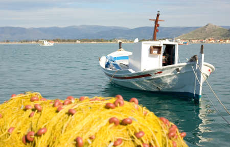 End of fishing day. White boat and yellow fishing net with clear blue sea photo