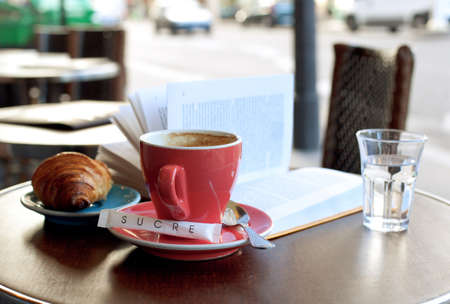 Breakfast in a Parisian street cafe - cup of coffee, croissant and book photo