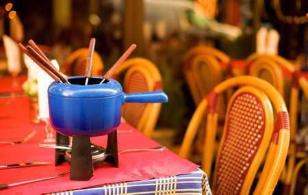 Parisian street cafe with an earthenware pot (caquelon) for fondue photo