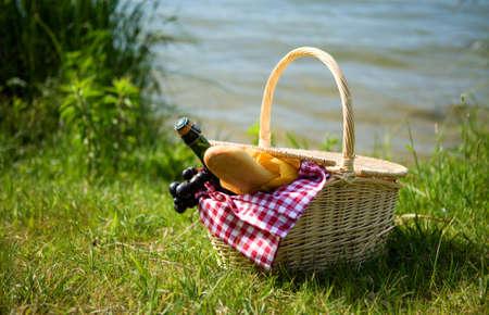 canastas con frutas: Cesta de picnic con botella de sidra y la alimentaci�n cerca del agua Foto de archivo
