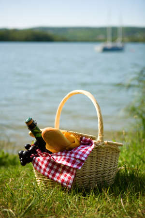 Picnic basket with food and cider bottle near the water photo