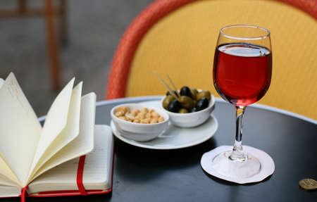 Parisian street cafe table with traditional French aperitif kir cassis, nibbles and personal organizer