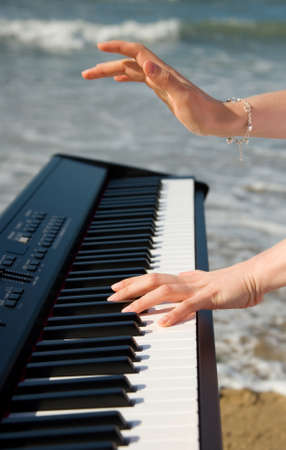 Playing music at the seashore. Beautiful female hands, piano keyboard and ocean or sea in the background photo