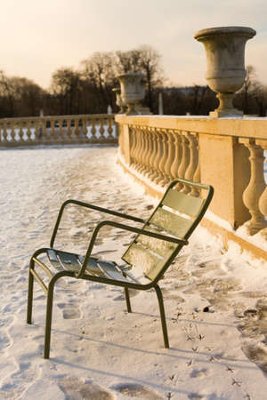 a rare: Rare snowy day in Paris. Lots of snow and traditional chair in the Luxembourg Garden