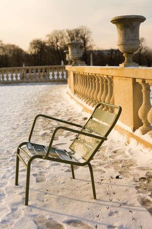 precipitaci�n: Raro d�a de nieve en Par�s. Mucha nieve y una silla tradicional en el Jard�n de Luxemburgo Foto de archivo