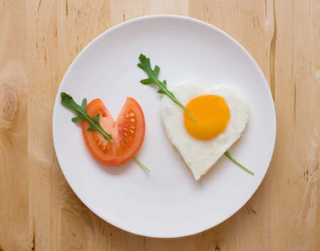 Happy Valentine Day! Fried egg and slice of tomato in the shape of two hearts pierced with two arrows photo