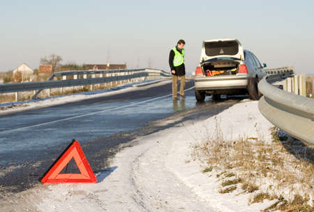 winter break: Road accident. Warning triangle and driver in a reflective safety vest near the broken car. Focus on triangle Stock Photo