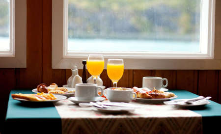 Delicious breakfast served on a table near the window at rainy day