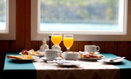 jus orange glazen: Heerlijk ontbijt geserveerd op een tafel bij het raam op regenachtige dag
