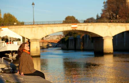 Beautiful woman relaxing at Paris embankment Banco de Imagens