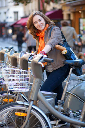 parisian: Beautiful girl with baguttes taking a bike for rent in Paris Stock Photo