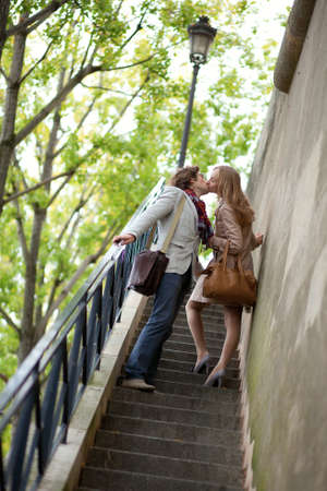 Romantic couple in Paris, kissing at the stairs photo