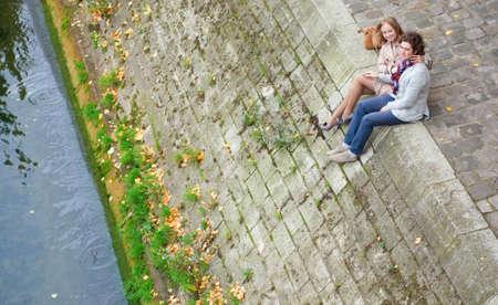 Romantic couple in Paris, sitting at the Seine embankment photo