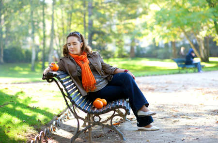 Beautiful young woman with oranges in park at spring or fall photo