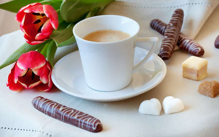 Morning coffee with cookies, heart-shaped pieces of sugar and flowers photo
