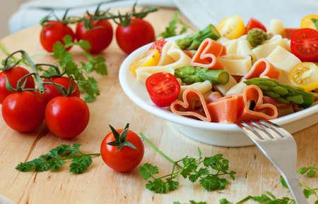 makarony: Romantyczna kolacja. Pyszne w kształcie serca, makaron z pomidorami, szparagami i świeżymi ziołami