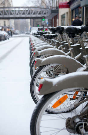Winter in Paris. Row of bicycles for rent covered with snow photo