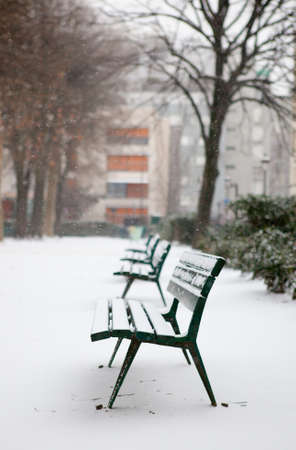 paris street: Winter in Paris. Benches in a park covered with snow Stock Photo