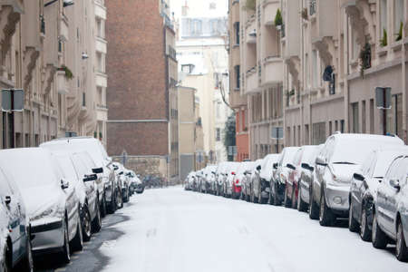 Winter in Paris. Parisian street with cars covered with snow photo