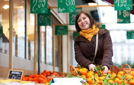 brune: Beautiful young girl buying mandarins at market Stock Photo