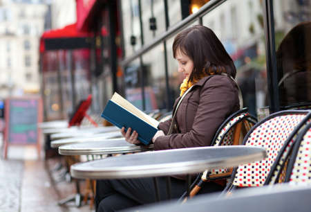 Beautiful young girl reading a book in Parisian street cafe photo