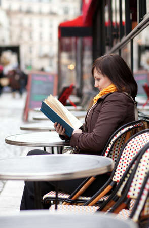 street cafe: Beautiful young girl reading a book in Parisian street cafe Stock Photo